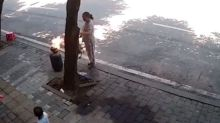 Woman drags gas cylinder on road after accidentally igniting it in China