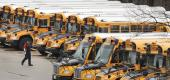 A worker passes public school buses parked at a depot in Manchester, N.H. (AP)