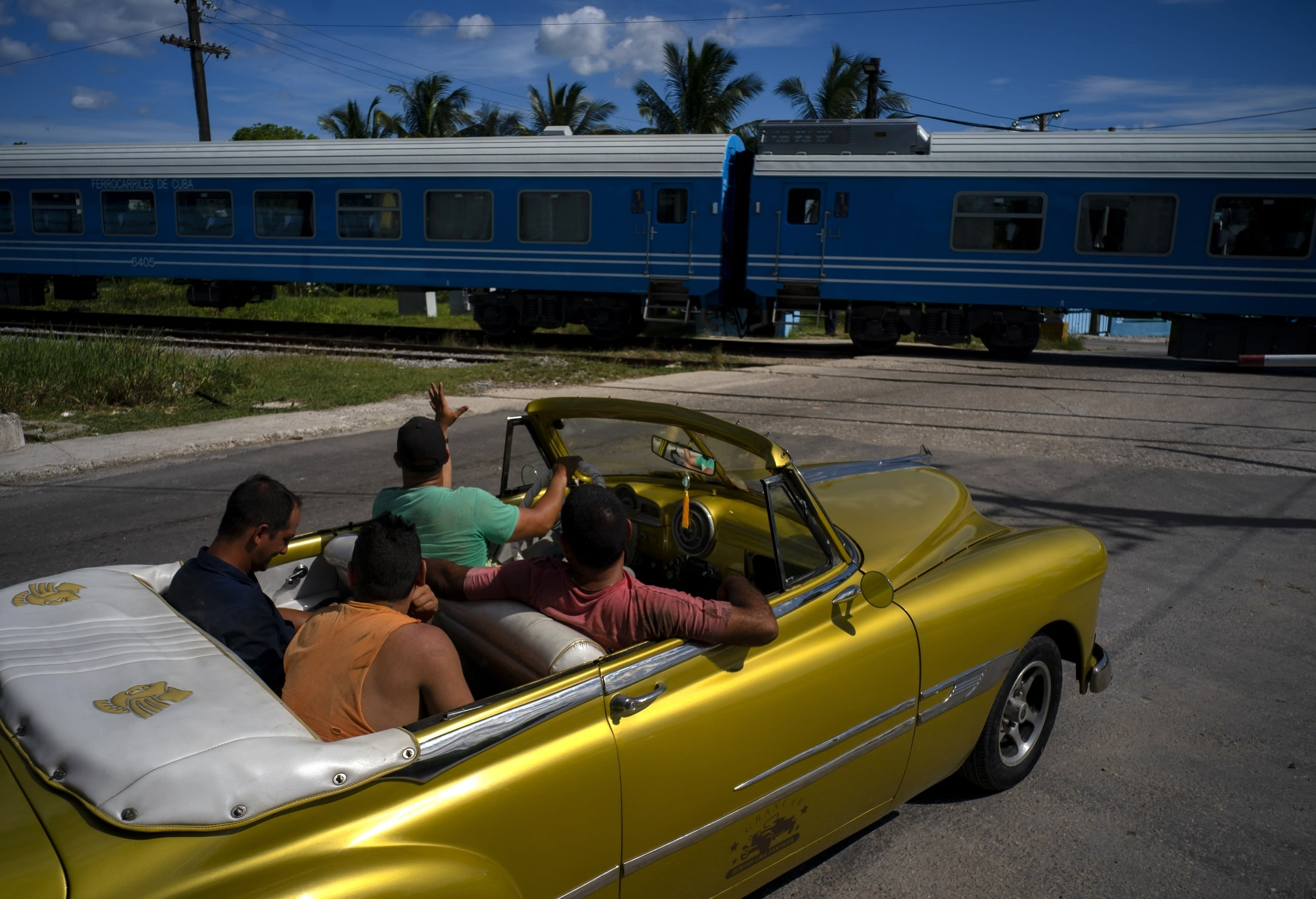 A driver in an American classic car waves as the first train using new equipment from China rides past, in Havana, Cuba, Saturday, July 13, 2019. The first train using new equipment from China pulled out of Havana Saturday, hauling passengers on the start of a 915-kilometer (516-mile) journey to the eastern end of the island as the government tries to overhaul the country's aging and decrepit rail system. (AP Photo/Ramon Espinosa)