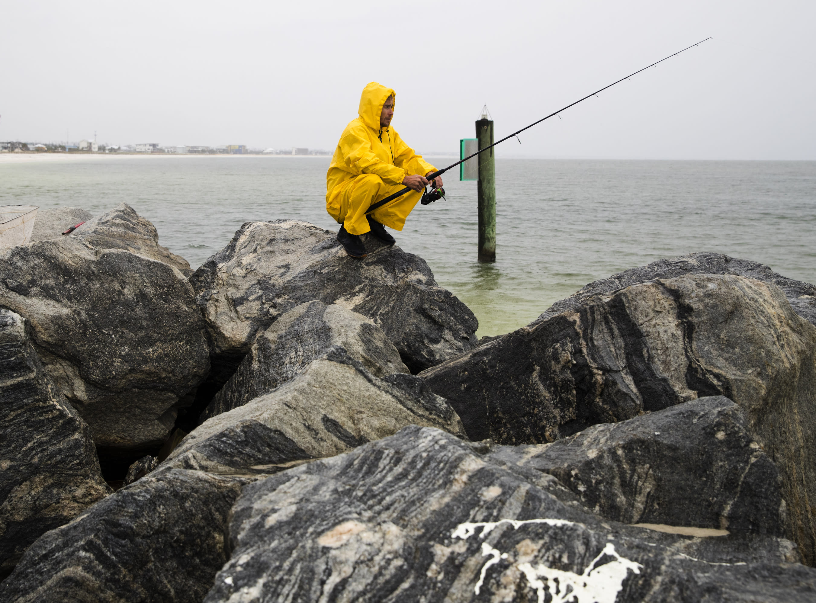 Michael Foster fishes as Tropical Storm Nestor approaches, Friday, Oct. 18, 2019 in Mexico Beach, Fla.. Forecasters say a disturbance moving through the Gulf of Mexico has become Tropical Storm Nestor. The National Hurricane Center says high winds and dangerous storm surge are likely along parts of the northern Gulf Coast. Conditions are expected to deteriorate Friday into early Saturday. (Joshua Boucher/News Herald via AP)