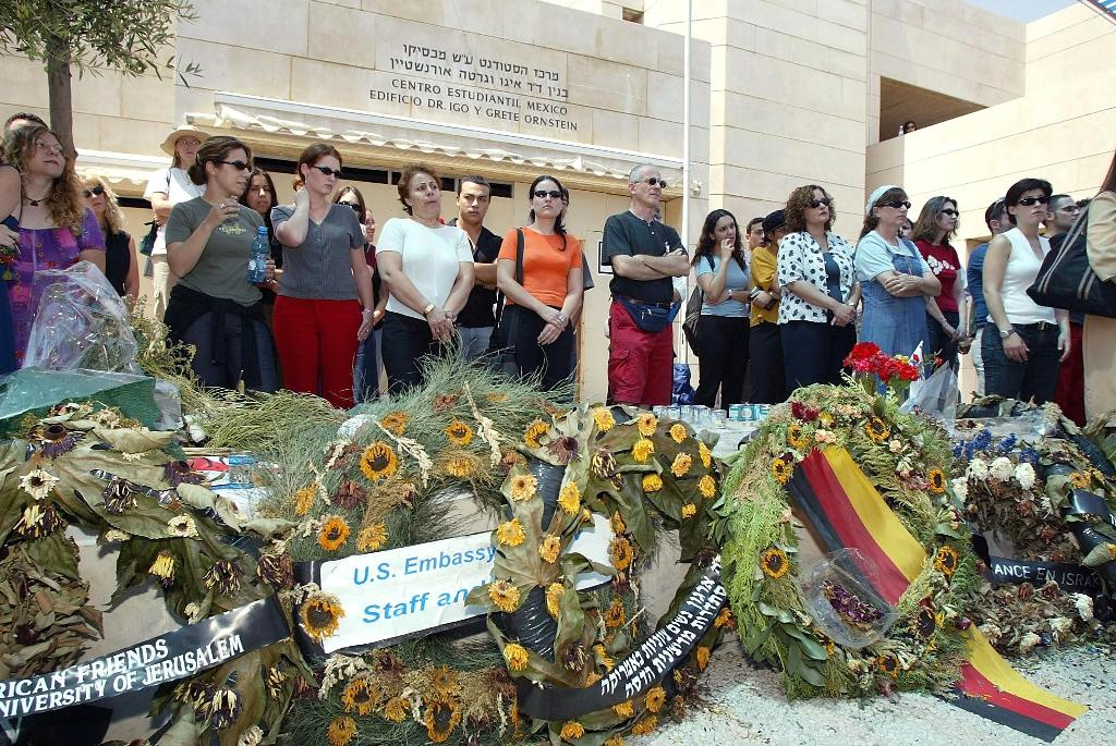 Attendants stand next to the memorial site of the Hebrew University in Jerusalem during a service on August 7, 2002, for the victims of the July 31 bomb attack