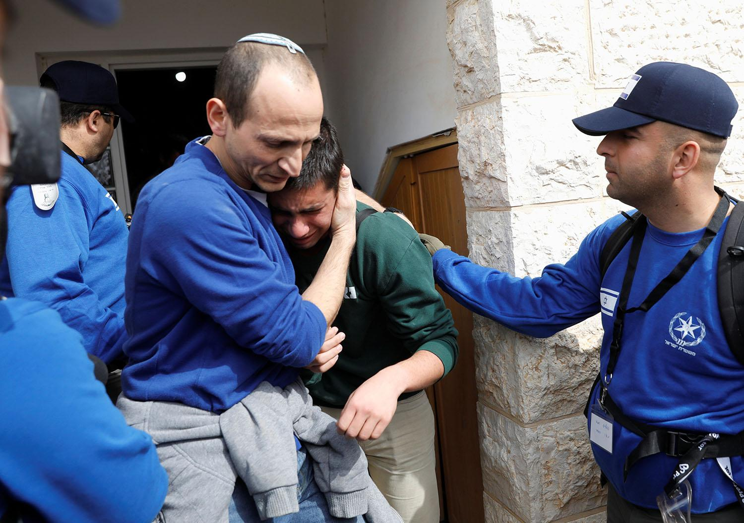 <p>Israeli police comfort a pro-settlement activist during an operation by Israeli forces to evict settlers from the West Bank settlement of Ofra, Tuesday, Feb. 28, 2017. Israeli forces began evacuating nine homes in the settlement following a Supreme Court decision that ruled they were built on private Palestinian land. REUTERS/Ronen Zvulun </p>