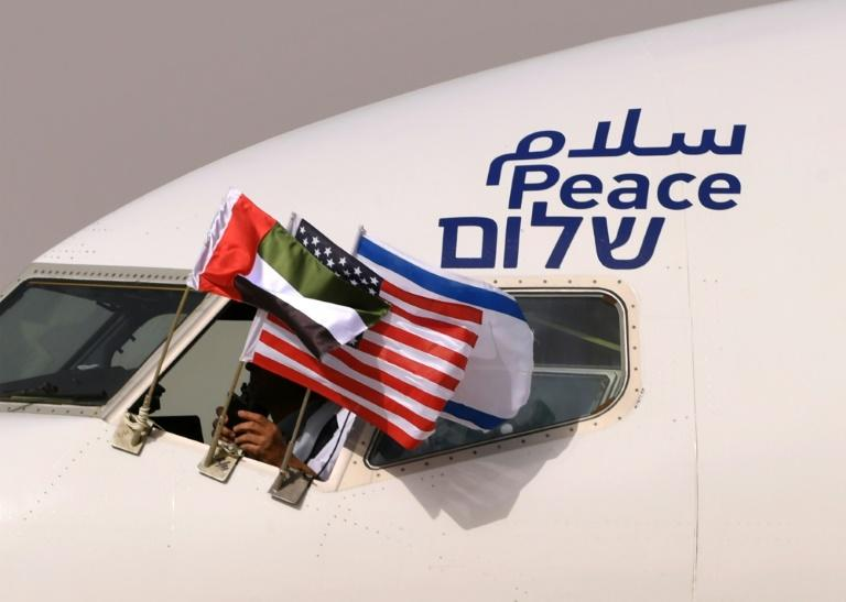 """The Emirati, US and Israeli flags fly from the cockpit window of an Israeli El Al aircraft below the word """"peace"""" in Arabic, English and Hebrew, upon its arrival at the Abu Dhabi airport Monday"""