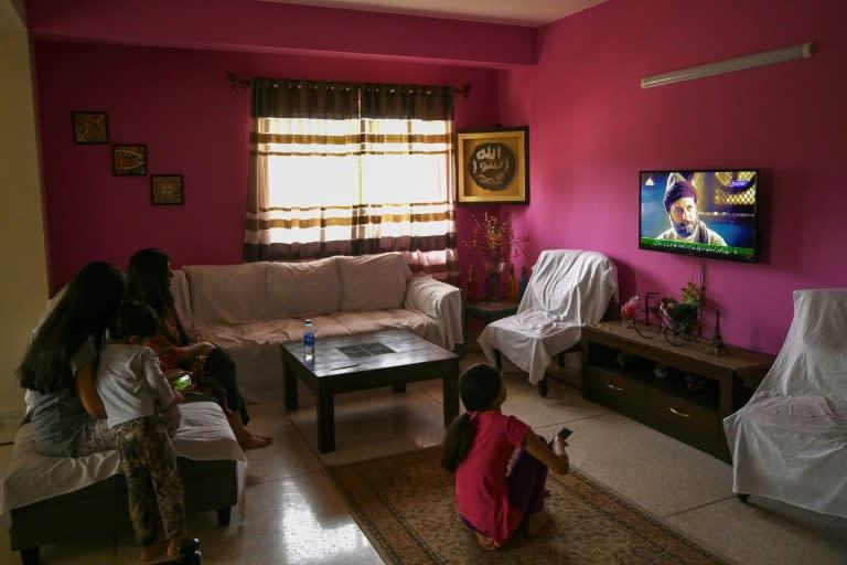 A Pakistani family enjoys the show Resurrection: Ertugrul in the capital Islamabad (AFP Photo/Aamir QURESHI)
