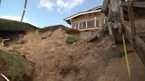 Surfer's home pounded by waves, sliding into ocean