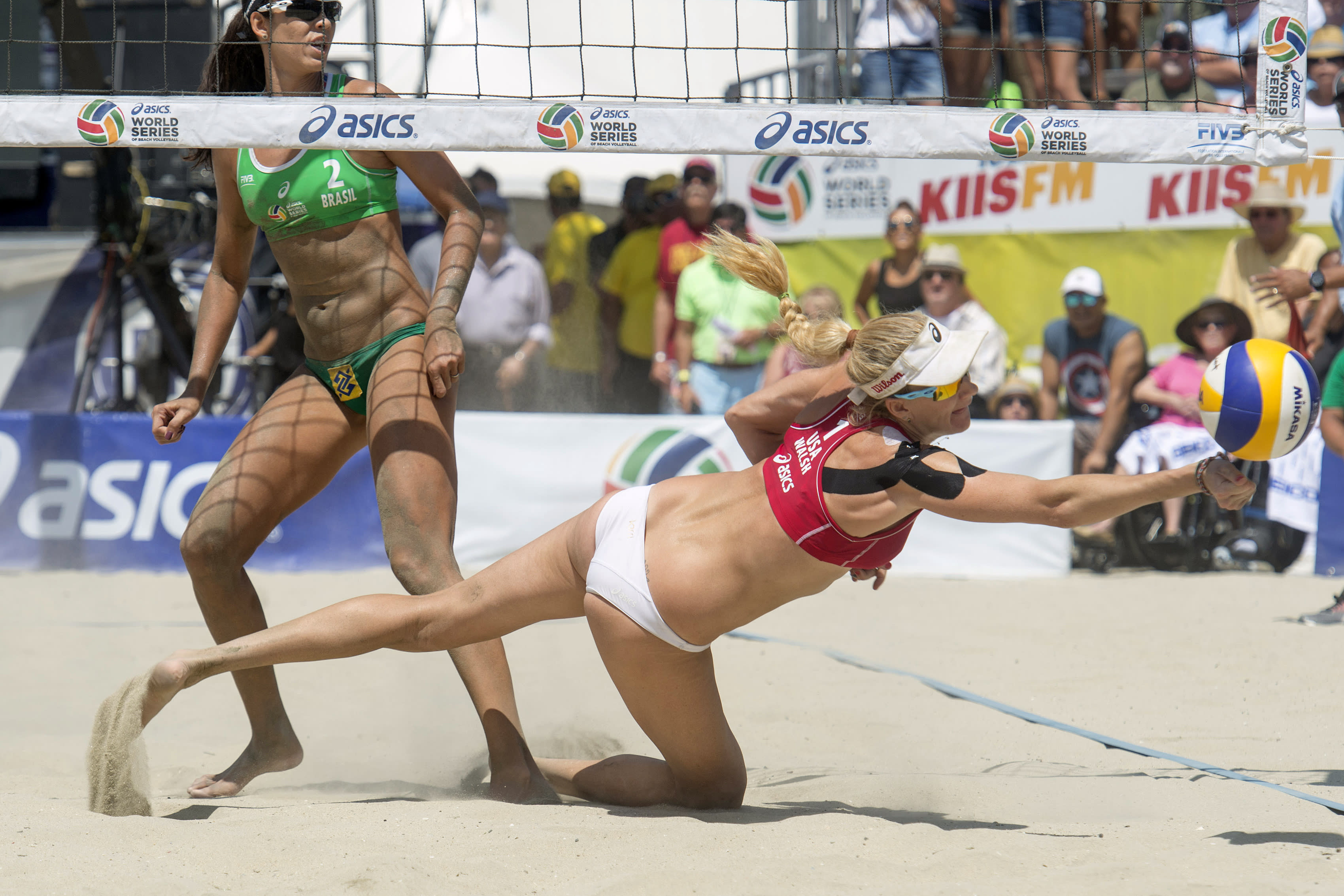 FILE - In this Aug. 23, 2015, file photo, Kerri Walsh Jennings can't get to the ball in the gold medal match at the FIVB World Series of Beach Volleyball at Alamitos Beach in Long Beach, Calif. Organizers of the AVP beach volleyball tour gathered at their Orange County war room to try to salvage as much as possible of their season as the cancellations mounted in the sports world. Ideas tossed out included everything from a fan-free setup on a local beach to playing in front of a green screen in a TV studio. But with the suspension of the NBA season, it became obvious that scrapping any events before June was the only choice. (Michael Goulding/The Orange County Register via AP, File)