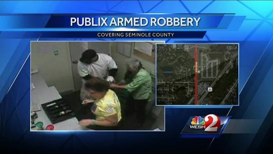 Surveillance video shows masked man rob grocery store employees