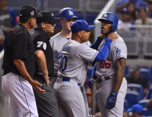 Yasiel Puig is held back by manager Dave Roberts after taking exception to Jose Urena's inside pitch. (Getty Images)