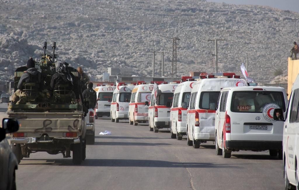 A convoy of ambulances transporting wounded civilians and rebels from the villages of Fuaa and Kafraya, the last two regime-held villages in Idlib province, is guarded as it heads towards the Cilvegozu crossing with Turkey on December 28, 2015 (AFP Photo/Omar Haj Kadour)