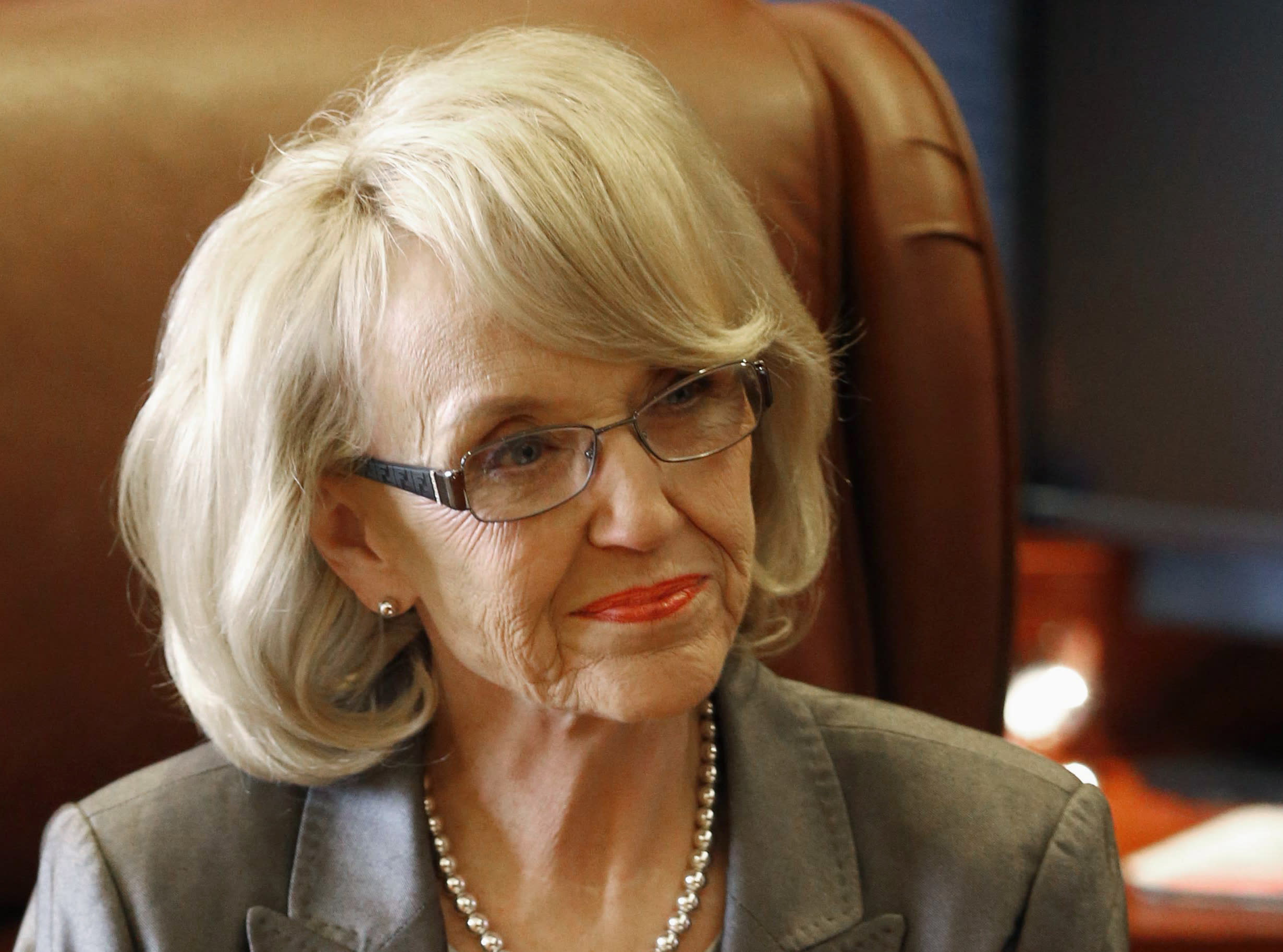 FILE - This Jan. 10, 2013 file photo show Arizona Gov. Jan Brewer in her office at the Capitol in Phoenix. Governors who reject health insurance for the poor under the federal health care overhaul could wind up in a politically awkward position on immigration: A quirk in the law means some U.S. citizens would be forced to go without coverage, while legal immigrants residing in the same state could still get it. Arizona officials called attention to the problem last week, when Brewer announced she would accept the expansion of Medicaid offered under Obama's law. Brewer had been a leading opponent of the overhaul, and her decision got widespread attention. Budget documents cited the immigration glitch as one of her reasons. (AP Photo/Matt York, File)