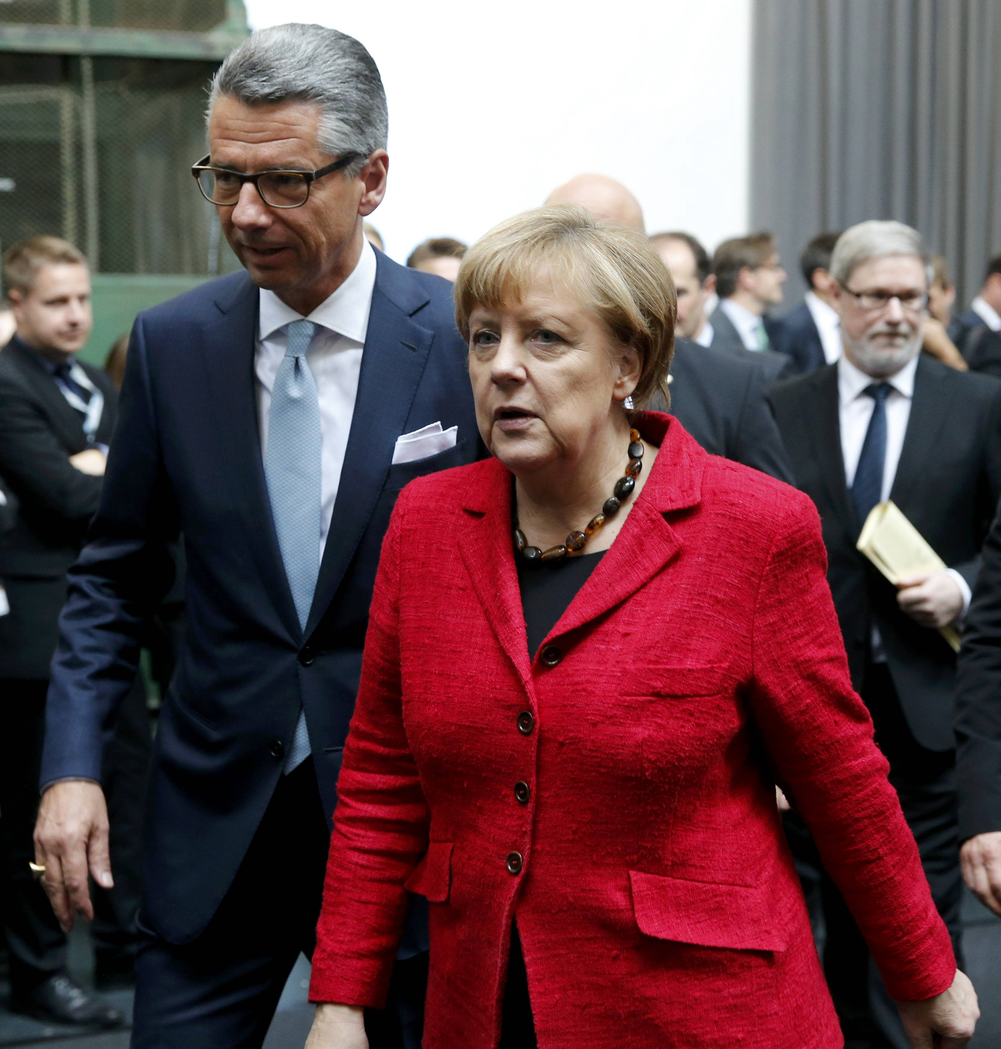 President of the Federation of German Industry (BDI) Ulrich Grillo (L) and German Chancellor Angela Merkel leave the BDI's conference in Berlin, Germany, November 3, 2015. Merkel reiterated on Tuesday that a European-wide approach was needed to tackle the refugee crisis and that a fair distribution of migrants among member states was vital. REUTERS/Fabrizio Bensch