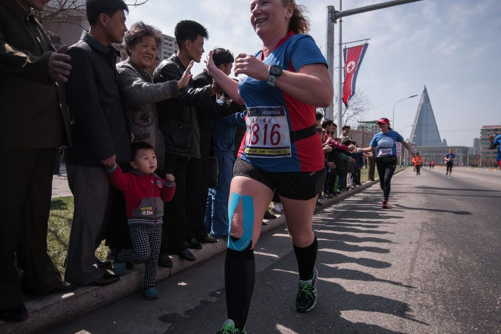Despite rising geopolitical tensions, knots of spectators gathered along the route, cheering the runners on and exchanging high-fives with them (AFP Photo/Ed JONES)