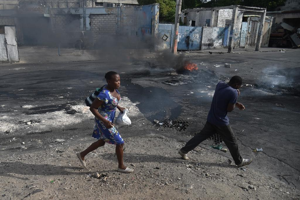 People walk past burning tires placed by protesters in the streets of Port-au-Prince (AFP Photo/HECTOR RETAMAL)