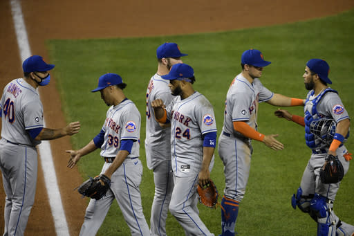 New York Mets' Wilson Ramos (40), Edwin Diaz (39), Robinson Cano (24), Robinson Chirinos, far right, and others celebrate after a baseball game against the Washington Nationals, Thursday, Sept. 24, 2020, in Washington. The Mets won 3-2. (AP Photo/Nick Wass)