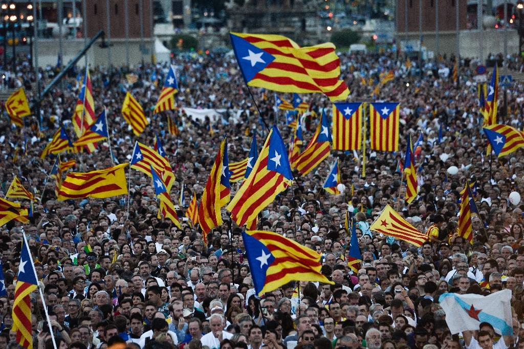 """People wave pro-independence flags during the Catalan independence coalition """"Junts pel Si"""" (Together for Yes) final campaign meeting in Barcelona on September 25, 2015 (AFP Photo/Josep Lago)"""