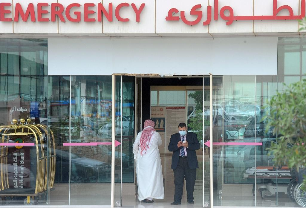 A man, wearing a mouth and nose mask, checks his phone as he leaves the hospital emergency department on April 27, 2014 in Riyadh (AFP Photo/Fayez Nureldine)