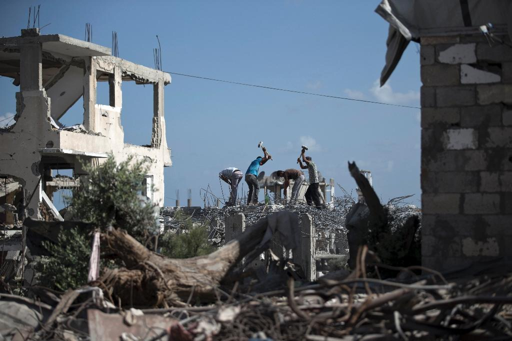 Palestinian workers remove the rubble of a building that was destroyed during the 50-day war between Israel and Hamas militants in the summer of 2014, on August 25, 2015 in Gaza City's eastern suburb of al-Shejaiya (AFP Photo/Mohammed Abed)