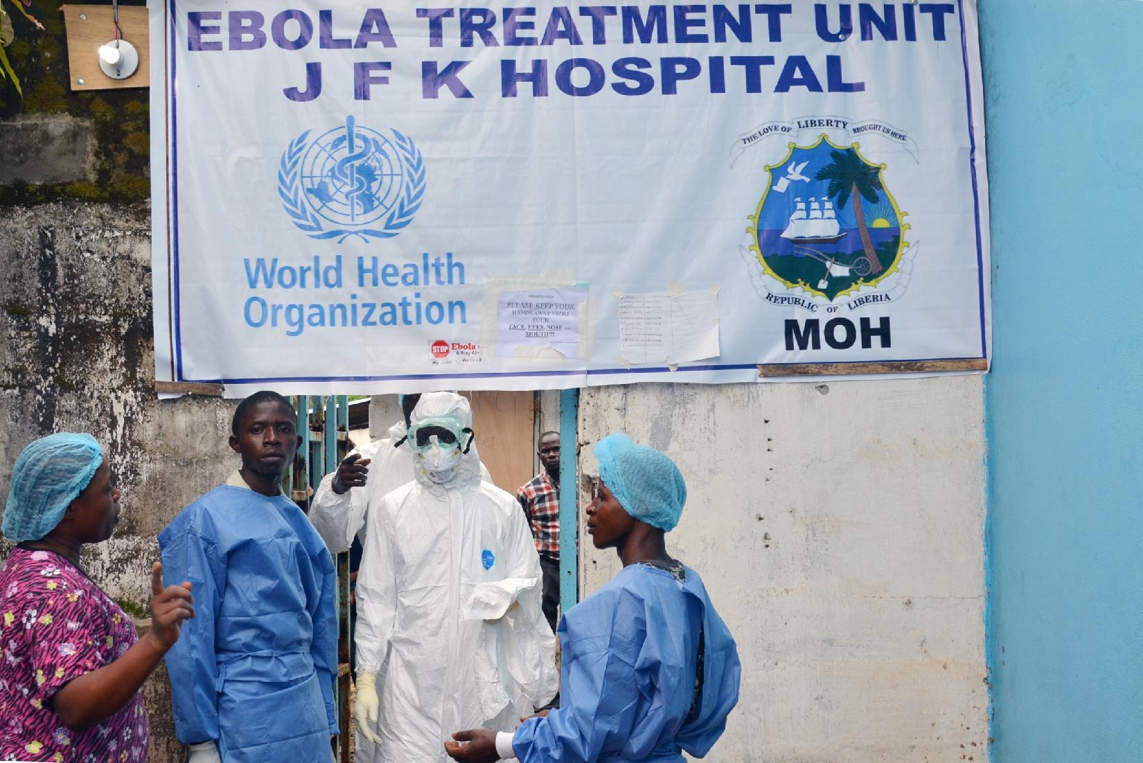 Health workers in protective gear stand at the entrance of the Ebola treatment unit of the John F. Kennedy Medical Center in the Liberian capital Monrovia on October 13, 2014
