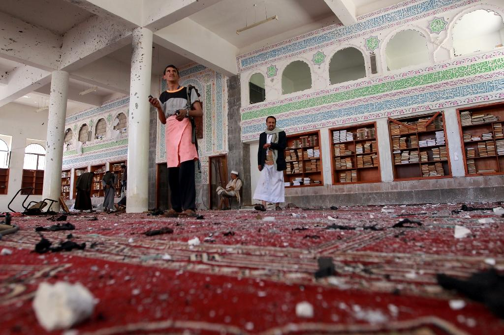 Armed men inspect the damage following a bomb explosion at the Badr mosque in southern Sanaa on March 20, 2015 (AFP Photo/Mohammed Huwais)