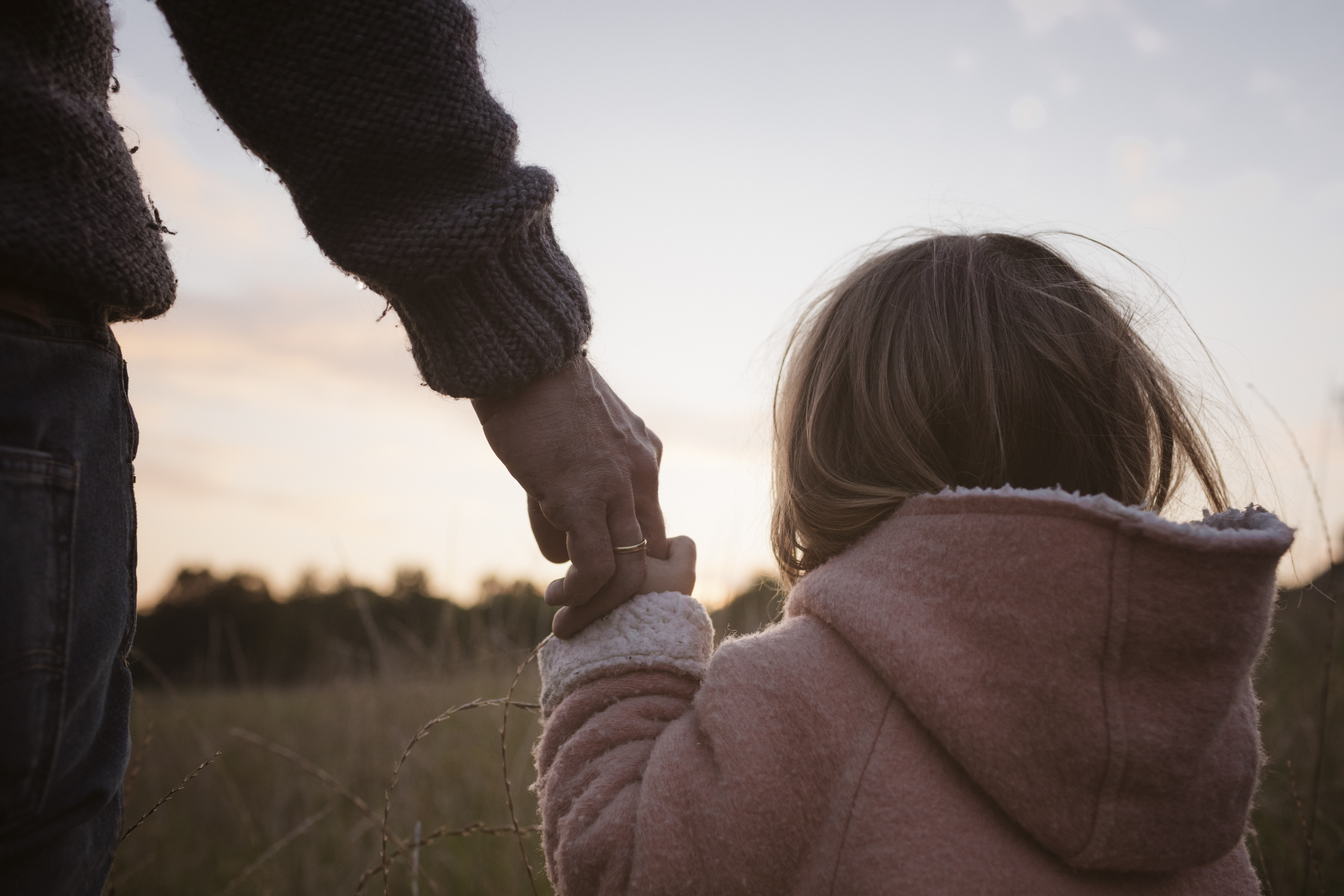 Father with daughter standing at a field at sunrise