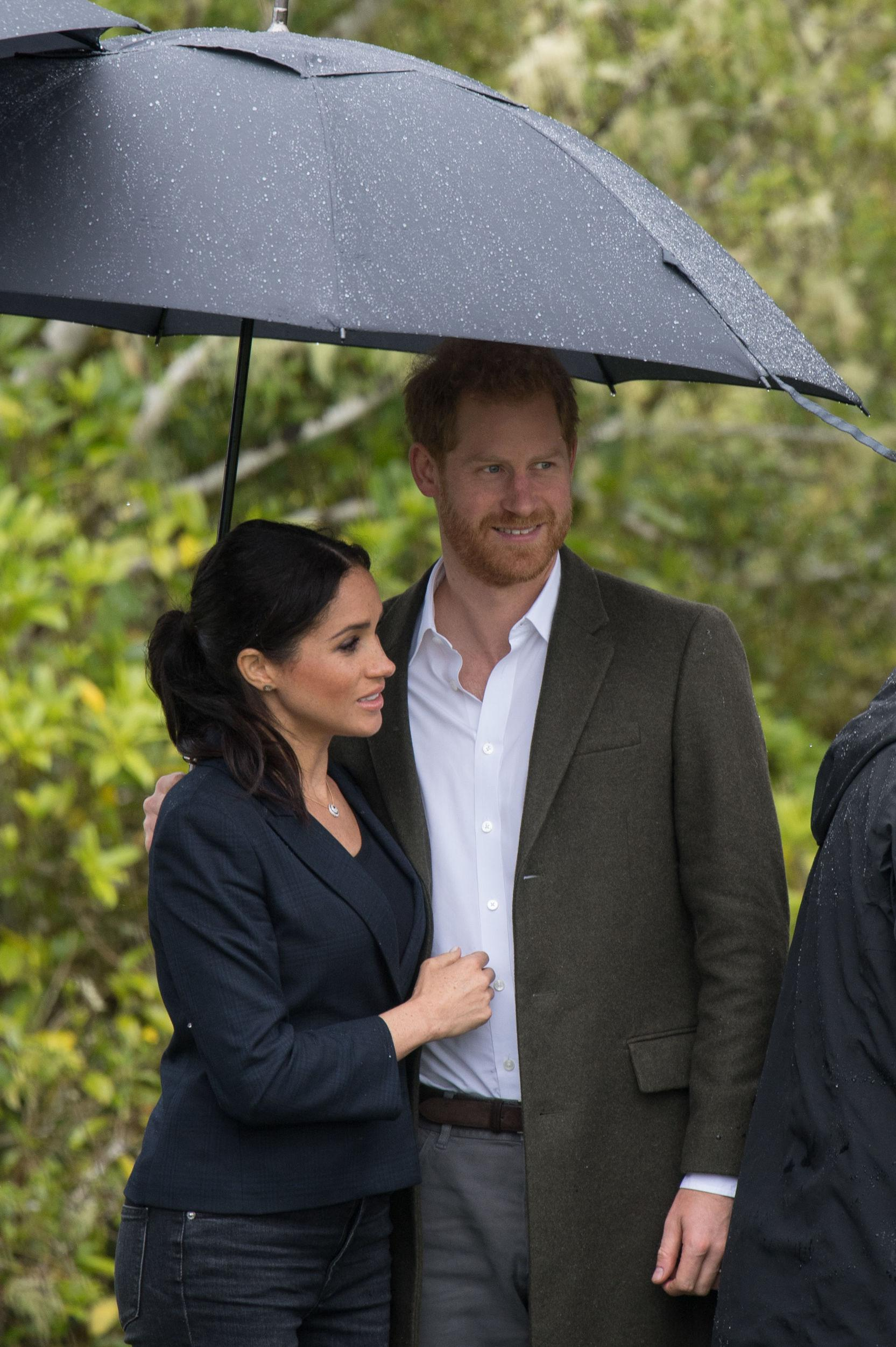 The Duke and Duchess of Sussex stand under an umbrella during a heavy downpour of rain as they attend a dedication of an area of bush to the Queen's Commonwealth Canopy, in Redvale on the North Shore, on day three of the royal couple's tour of New Zealand.