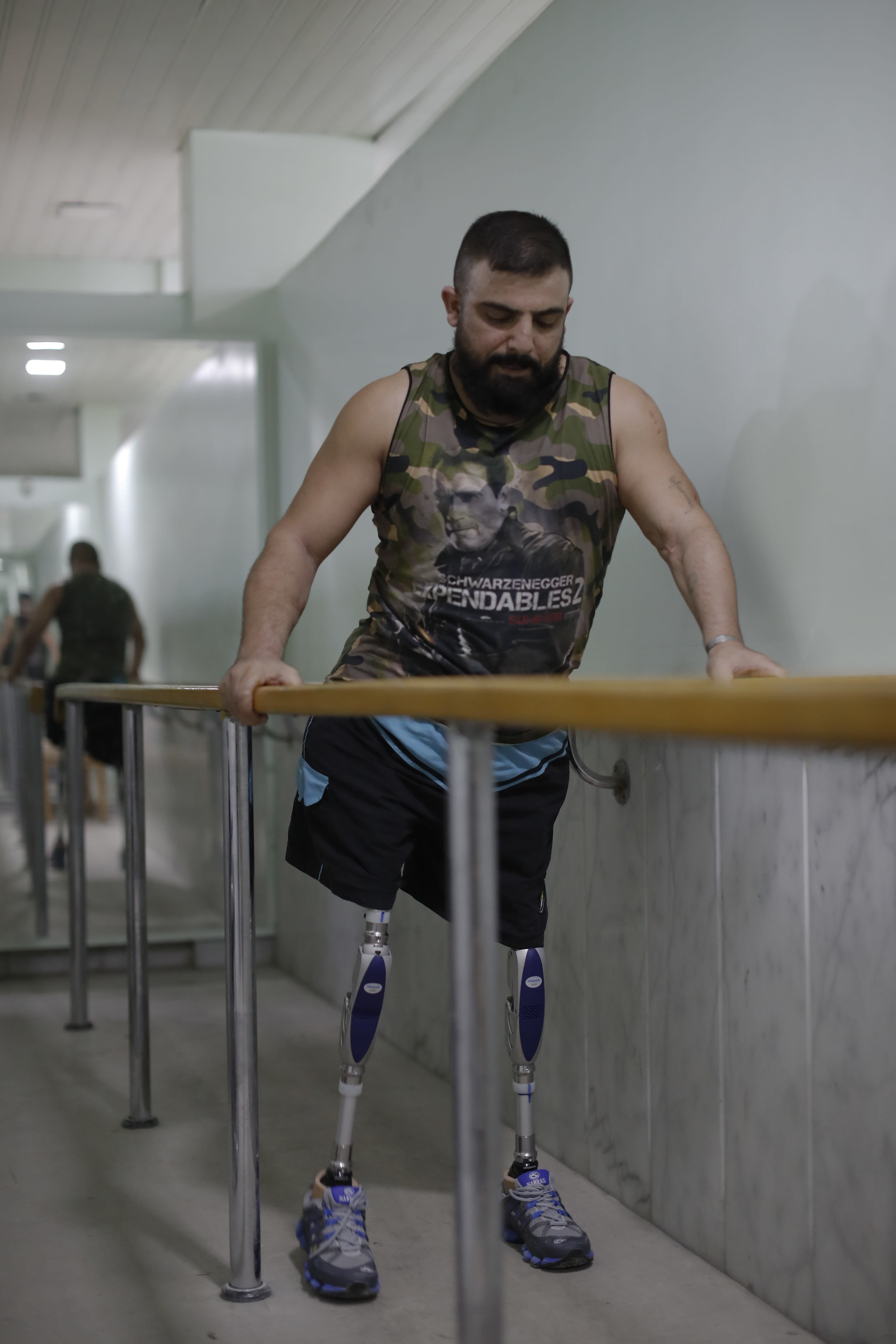 <p>Haidar Hussein, a Syrian soldier who lost his legs while fighting on the frontlines in Syria's war, walks on prosthetics during a physical therapy session at the Ahmad Hamish Martyr hospital in Damascus, Syria. (Photo: Hassan Ammar/AP) </p>