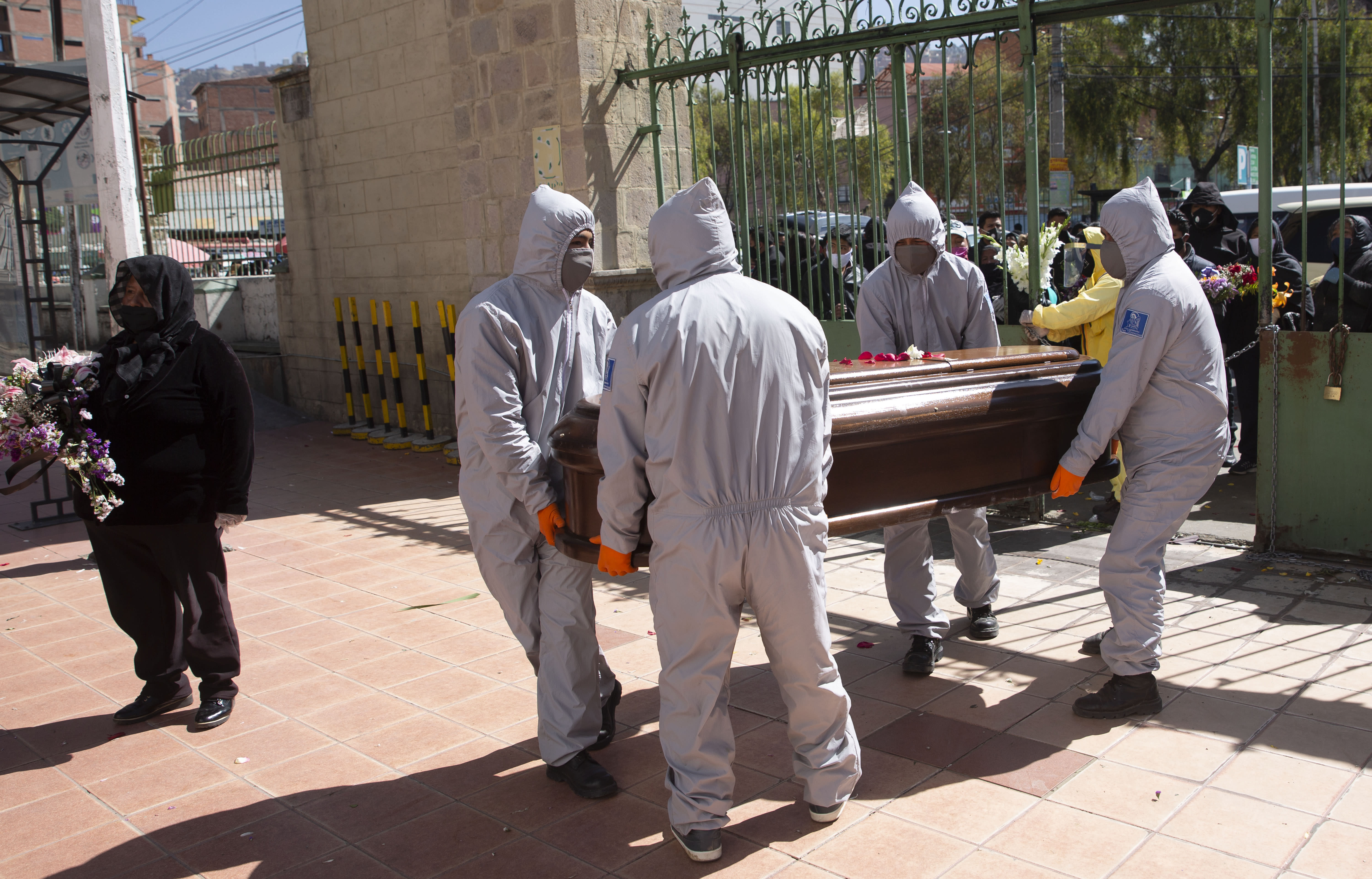 Funeral home workers wearing full protective gear as a precaution against the spread of the new coronavirus, carry the coffin of a man, whose death was not related to COVID-19, into the General Cemetery in La Paz, Bolivia, Tuesday, July 21, 2020. (AP Photo/Juan Karita)