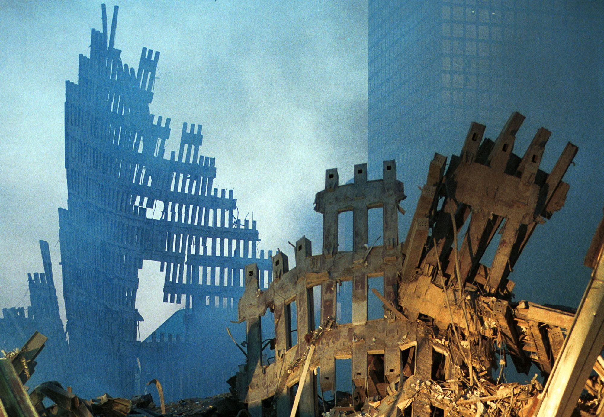 <p>Early morning light hits the smoke and wreckage of the World Trade Center September 13, 2001 in New York City, two days after the twin towers were destroyed when hit by two hijacked passenger jets. (Photo by Chris Hondros/Getty Images) </p>