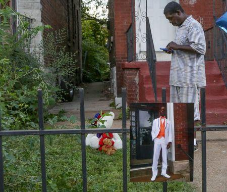 The father of Mansur Ball-Bey stands in front of the steps where police shot his son as a photo of Mansur hangs on the fence in St. Louis