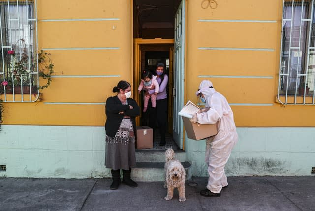 A city worker, dressed in protective gear, delivers a box of food to a vulnerable family in Santiago during a mandatory quarantine ordered by the Chilean government (Esteban Felix/AP)