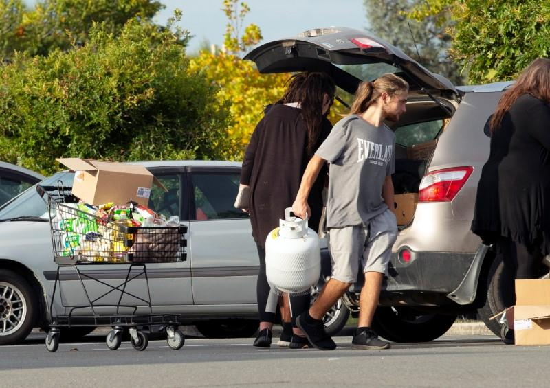 People take out products from their supermarket shopping cart and load them into their car outside Pak'nSave supermarket amid the spread of the coronavirus disease (COVID-19) in Christchurch