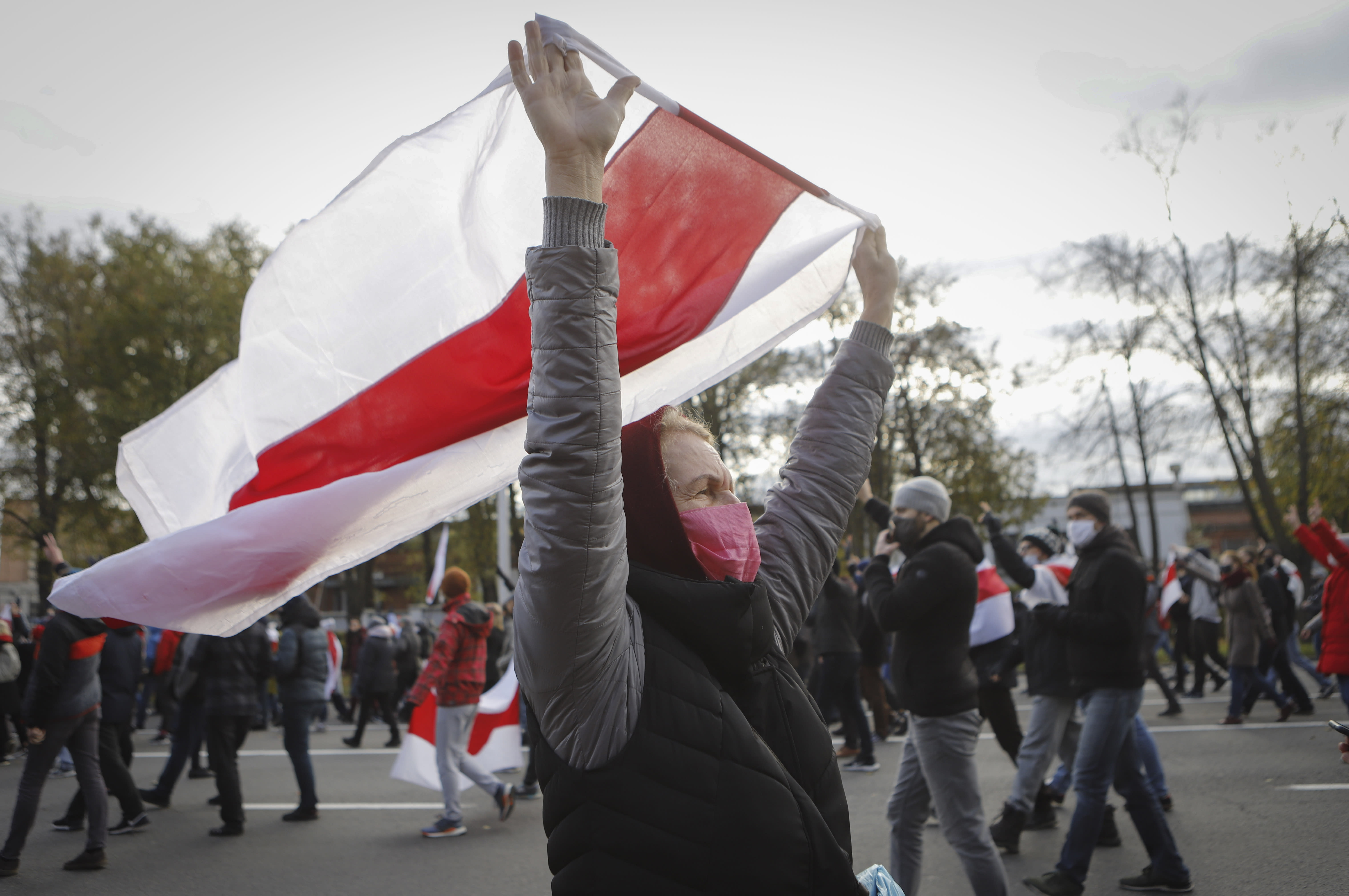 People with old Belarusian national flags march during an opposition rally to protest the official presidential election results in Minsk, Belarus, Sunday, Oct. 18, 2020. Hundreds of thousands of Belarusians have been protesting daily since the Aug. 9 presidential election. (AP Photo)