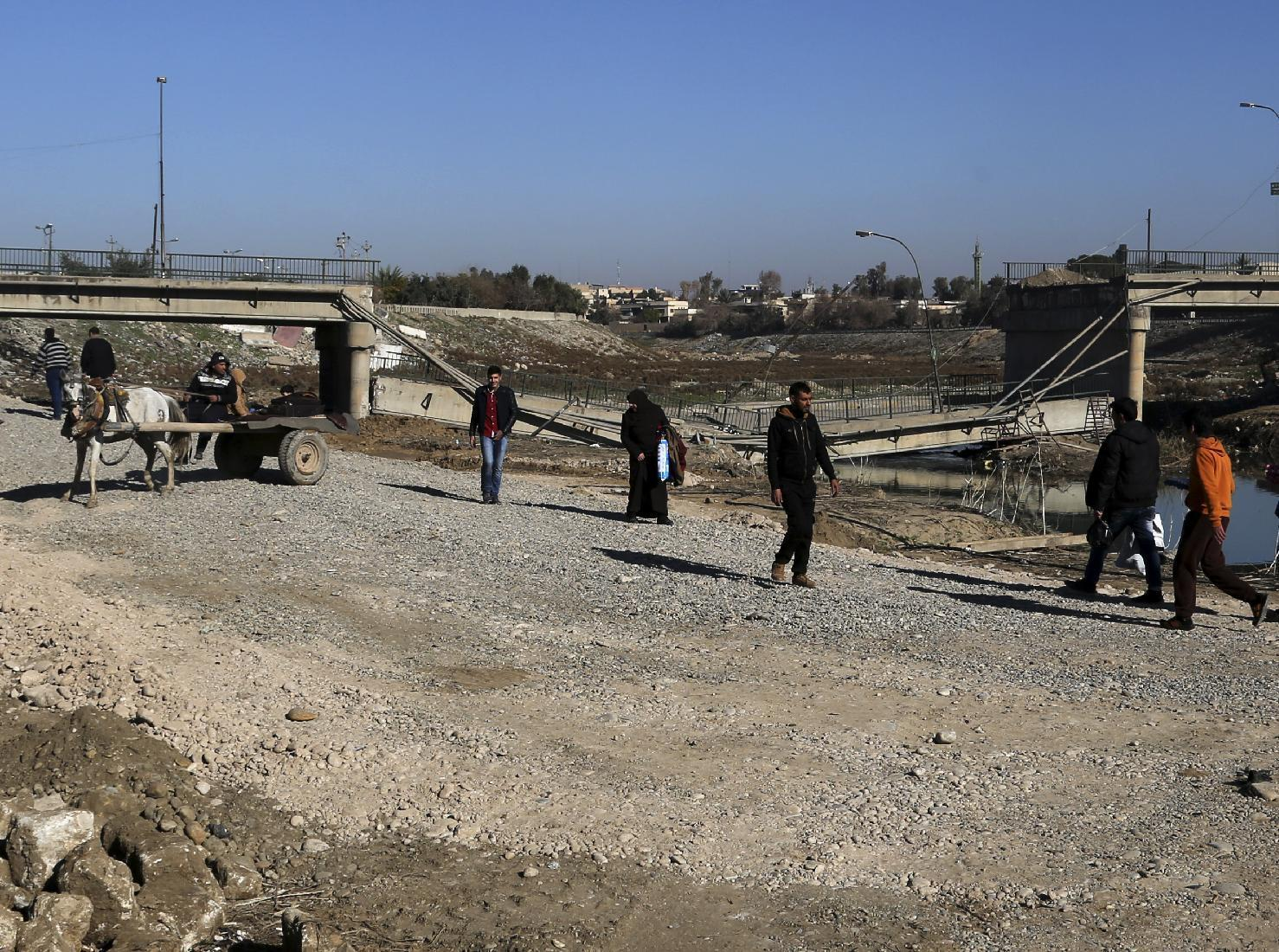 Civilians cross on a makeshift river next to a bridge destroyed by Islamic State militants in a neighborhood recently liberated from Islamic State on the eastern side of Mosul, Iraq, Thursday, Jan. 12, 2017. Small stalls and carts have sprung up outside the bombed-out restaurants and cafes in eastern Mosul, selling fresh vegetables, cigarettes and cellphones to the thousands of civilians still living in neighborhoods where the Iraqi military has driven out the extremists of the Islamic State group. (AP Photo/ Khalid Mohammed)