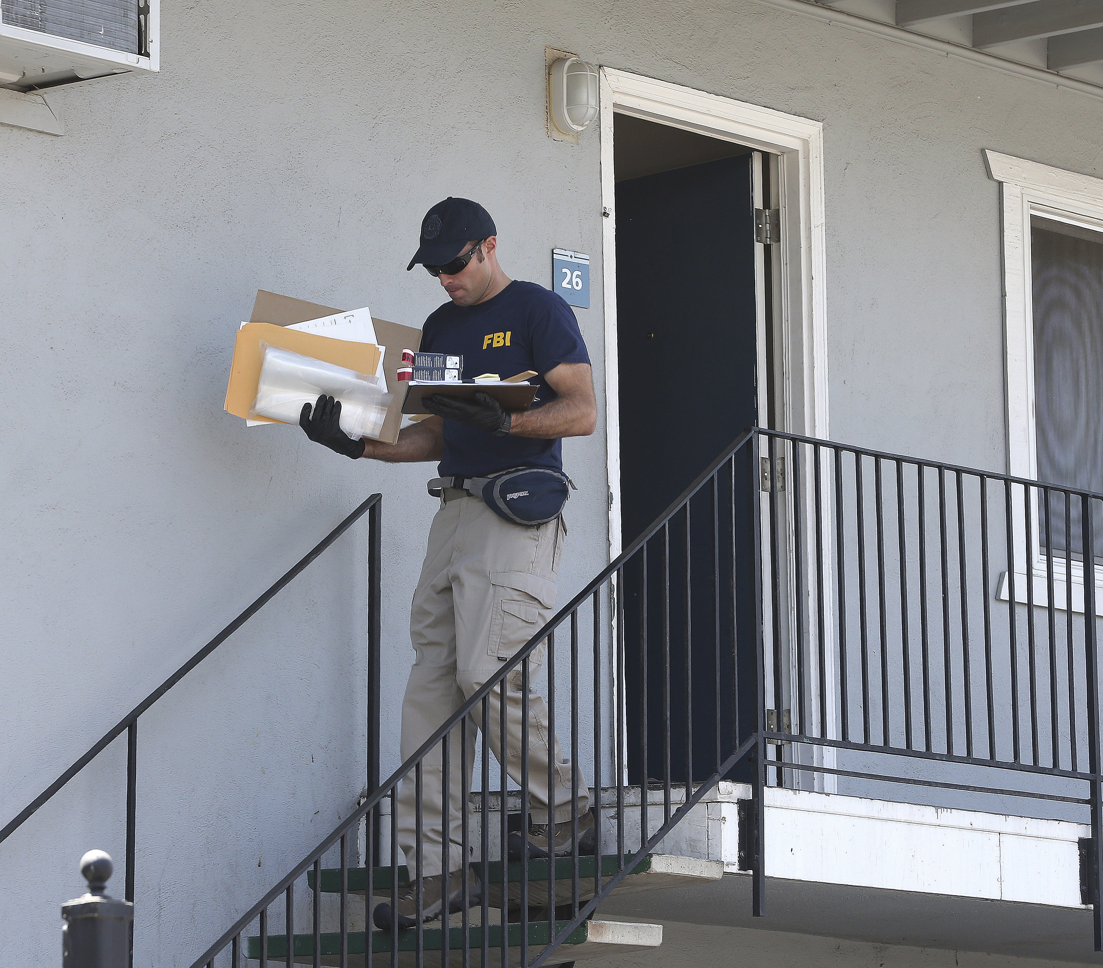A federal agent removes items from an apartment following the arrest of a 45-year-old Iraqi refugee, Omar Ameen, Wednesday, Aug. 15, 2018, in Sacramento, Calif. Ameen was arrested on a warrant alleging that he killed an Iraqi policeman in 2014 while serving with the Islamic State terror organization. (AP Photo/Rich Pedroncelli)