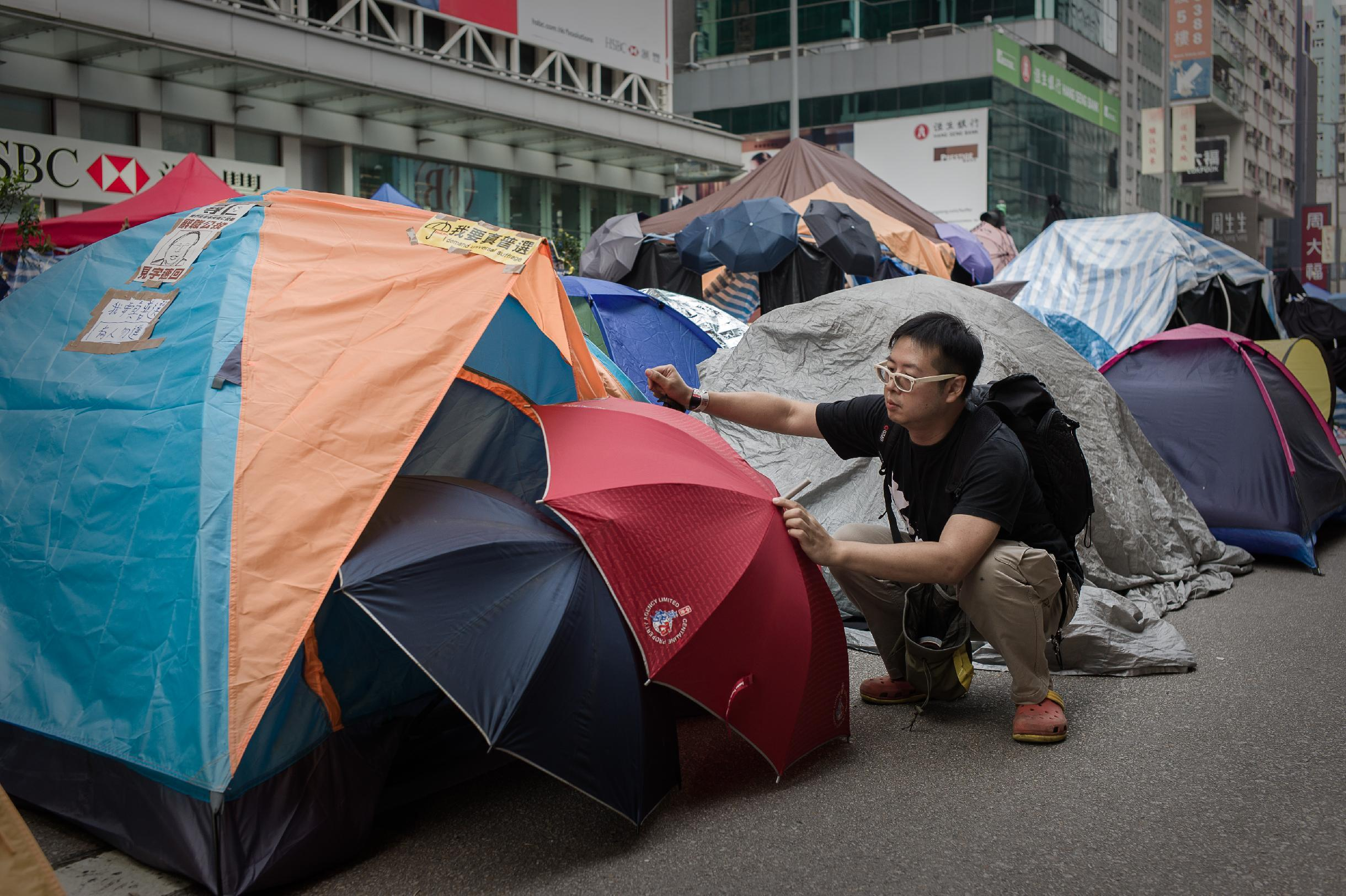 A pro-democracy protester adjusts umbrellas displayed by tents at a protest site in the Mongkok district of Hong Kong on November 12, 2014 (AFP Photo/Philippe Lopez)