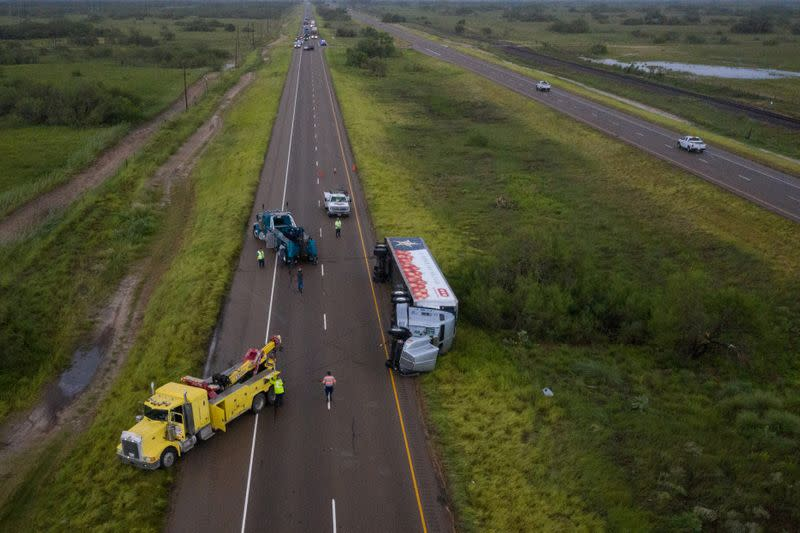 Tow trucks surround overturned truck in aftermath of Hurricane Hanna in Sarita, Texas