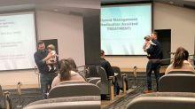 Professor unterrichtet mit Baby einer Studentin auf dem Arm