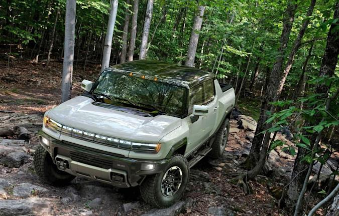 The Hummer EV navigating uneven rocky terrain in a forest.