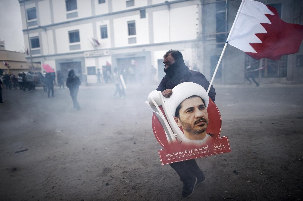 A Bahraini protester carries a placard showing Shiite opposition leader Sheikh Ali Salman during clashes with police in Manama, on February 13, 2015