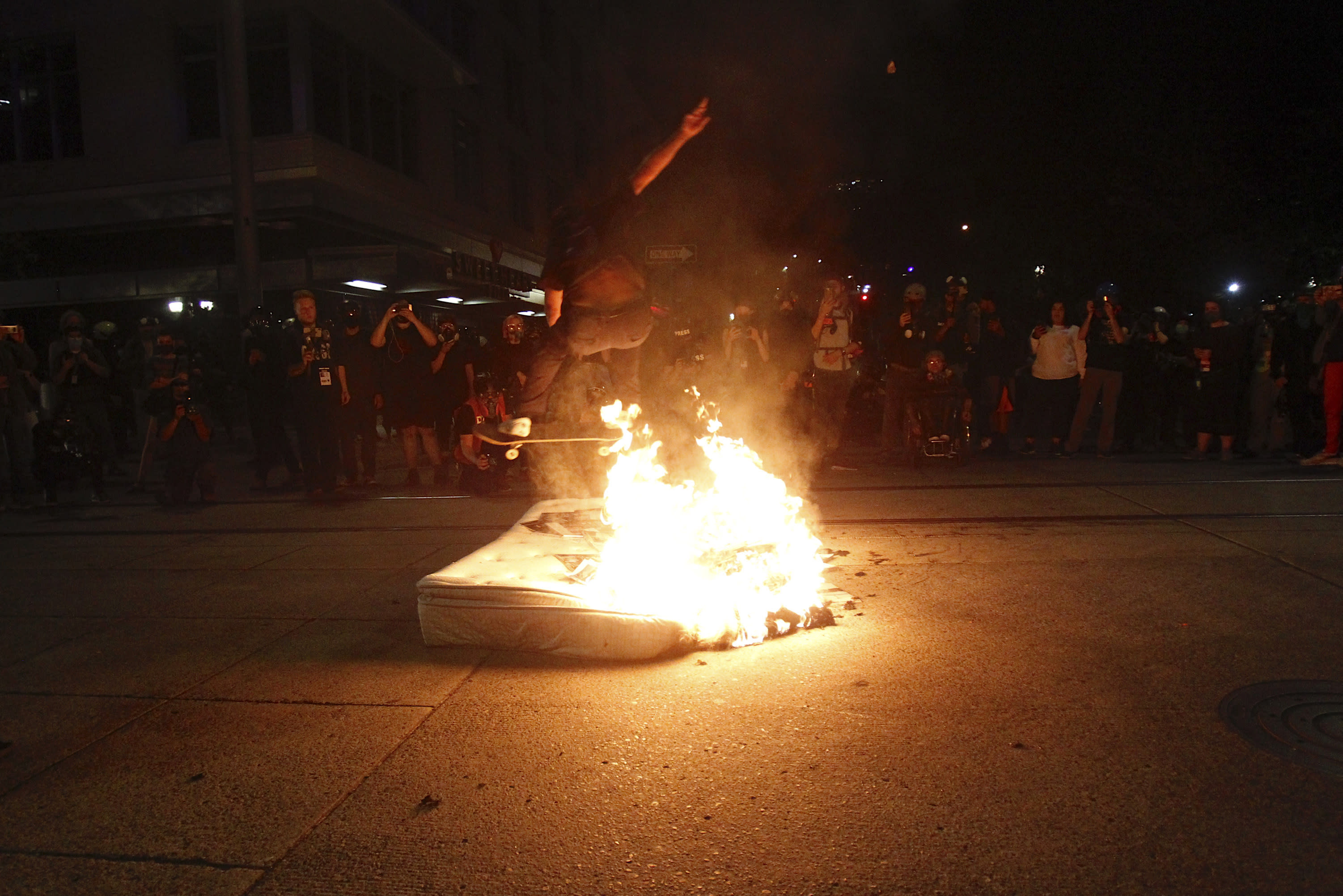 A protester jumps over a fire on his skateboard on Wednesday, Aug. 19, 2020. Protesters in Portland have clashed with federal agents for the first time since July in a demonstration that targeted a U.S. Immigration and Customs Enforcement building.(Sean Meagher/The Oregonian via AP)