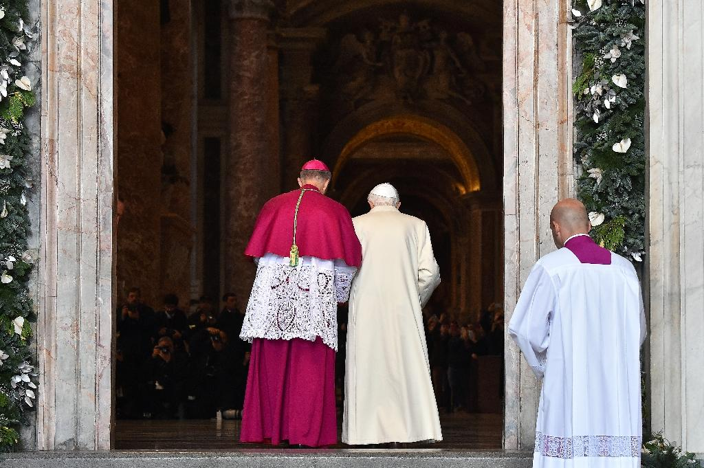 """Pope Emeritus Benedict XVI passes the """"Holy Door"""" opened by Pope Francis at St Peter's basilica to mark the start of the Jubilee Year of Mercy, on December 8, 2015 in the Vatican (AFP Photo/Vincenzo Pinto)"""