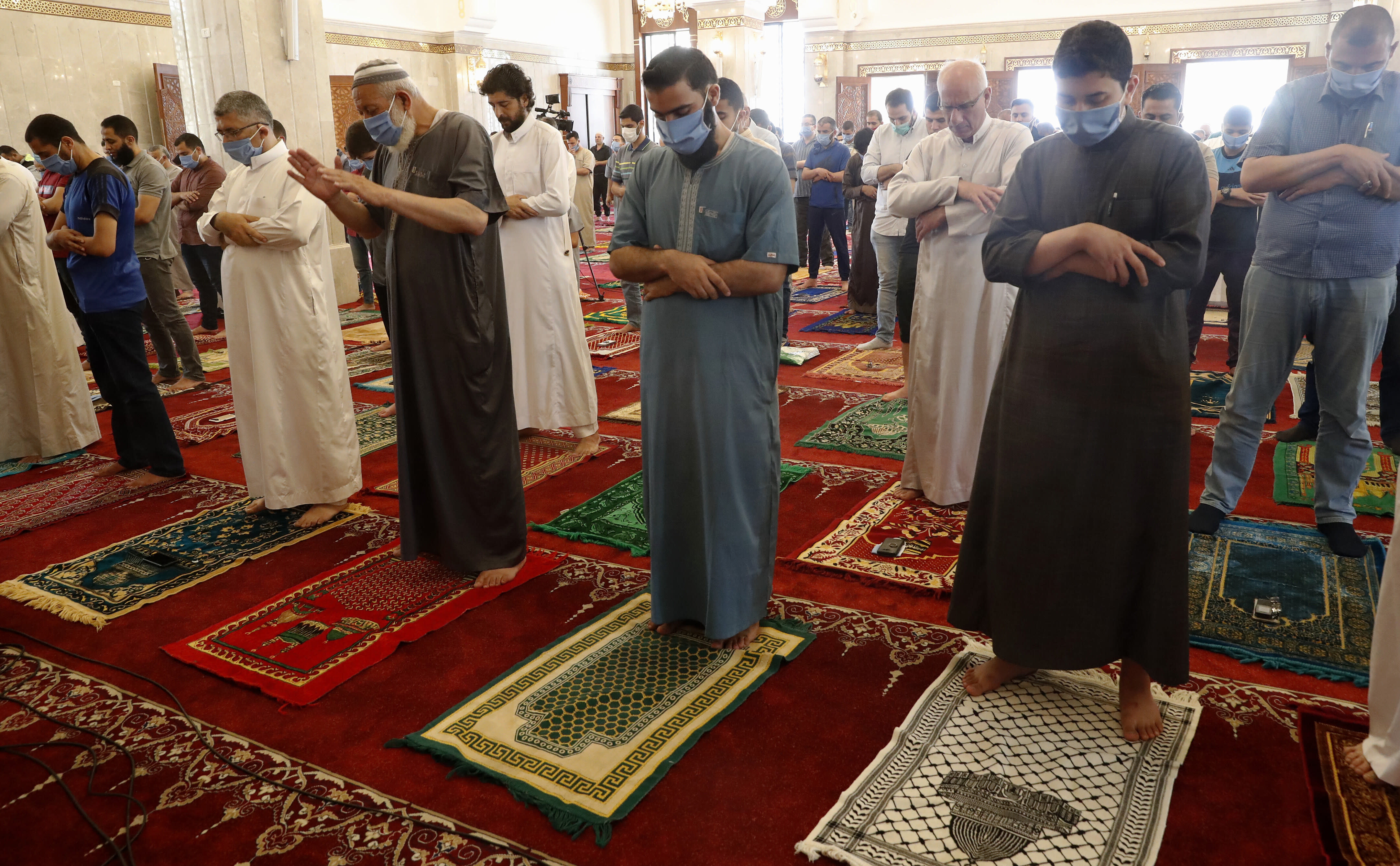 Palestinian worshippers wear protective face masks at the last Friday prayer of the holy fasting month of Ramadan, to prevent the spread of coronavirus pandemic, at al-Hasaynih beach mosque in Gaza City, Friday, May 22, 2020. Palestinian worshippers are filling Gaza's mosques as they open for the central Friday prayers after nearly two months of closure due to the coronavirus threat. (AP Photo/Adel Hana)