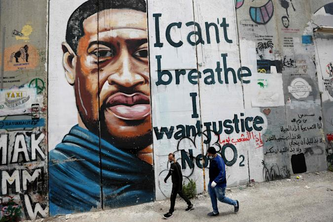 """People walk past a mural showing the face of George Floyd, an unarmed handcuffed black man who died after a white policeman knelt on his neck during an arrest in the US, painted on a section of Israel's controversial separation barrier in the city of Bethlehem in the occupied West Bank on March 31, 2021. - The teenager who took the viral video of George Floyd's death said on March 30, at the trial of the white police officer charged with killing the 46-year-old Black man that she knew at the time """"it wasn't right."""" Darnella Frazier, 18, was among the witnesses who gave emotional testimony on Tuesday at the high-profile trial of former Minneapolis police officer Derek Chauvin. Chauvin, 45, is charged with murder and manslaughter for his role in Floyd's May 25, 2020 death, which was captured on video by Frazier and seen by millions, sparking anti-racism protests around the globe. (Photo by Emmanuel DUNAND / AFP) (Photo by EMMANUEL DUNAND/AFP via Getty Images)"""