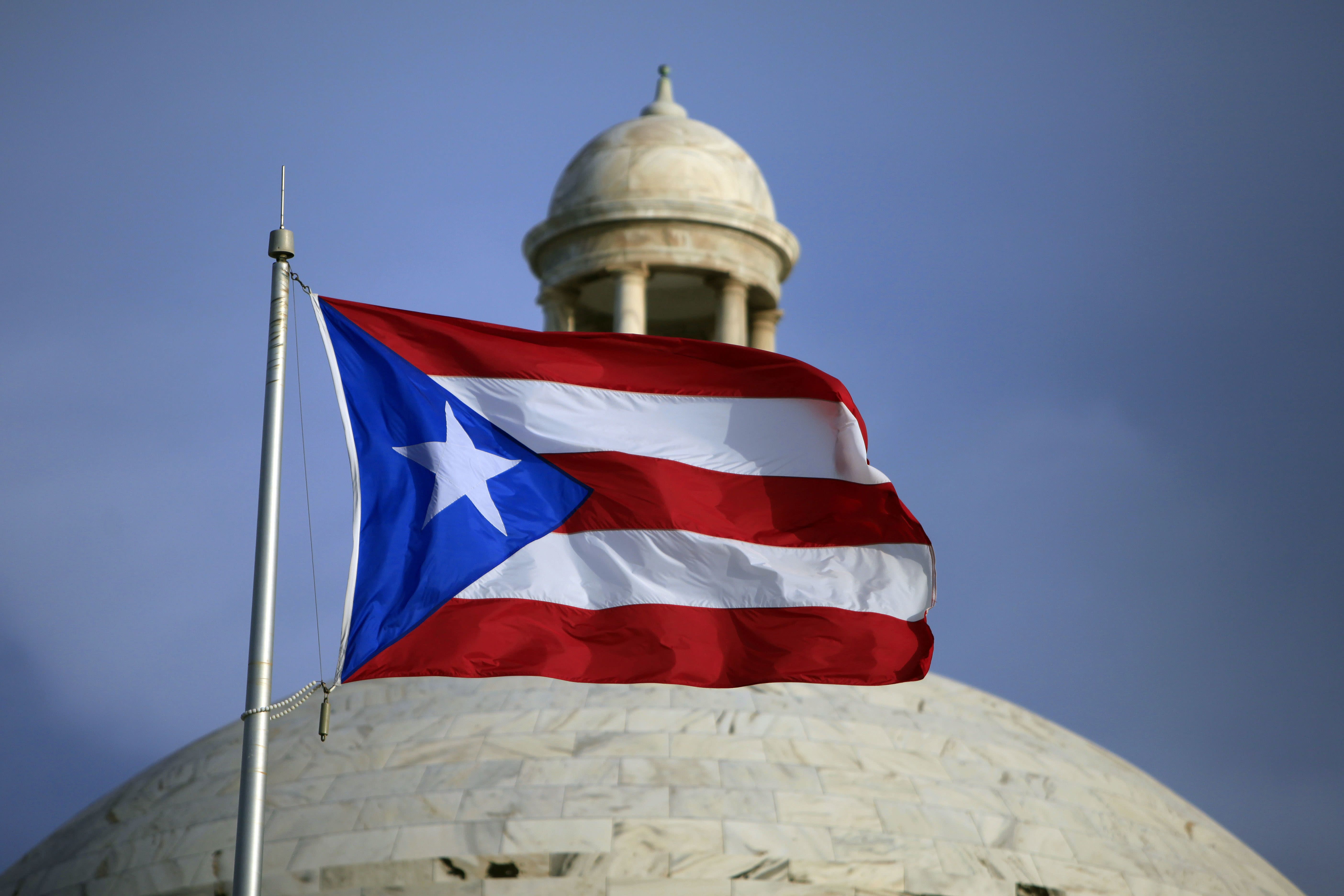 FILE - In this July 29, 2015 file photo, the Puerto Rican flag flies in front of Puerto Rico's Capitol as in San Juan, Puerto Rico. A federal control board that oversees Puerto Rico's finances approved on Wednesday, July 1, 2020, a new budget that largely suspends austerity measures and government cuts for one year as the U.S. territory struggles to recover from hurricanes, earthquakes and the pandemic. (AP Photo/Ricardo Arduengo, File)