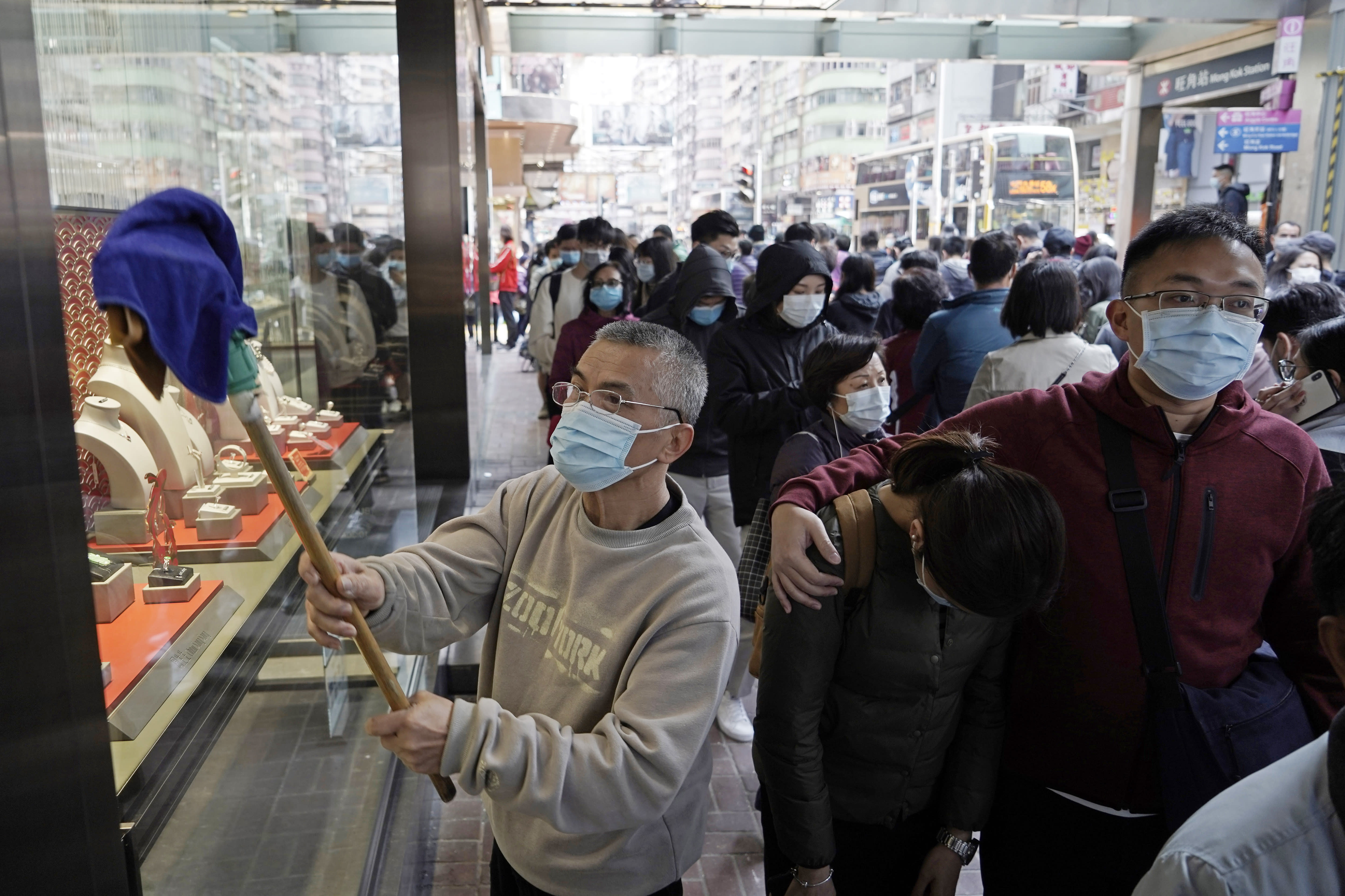 """A worker cleans a window of a jewelry shop as people queue to buy face masks in Hong Kong, Saturday, Feb, 1, 2020. China's death toll from a new virus has risen over 250 and a World Health Organization official says other governments need to prepare for""""domestic outbreak control"""" if the disease spreads. (AP Photo/Kin Cheung)"""