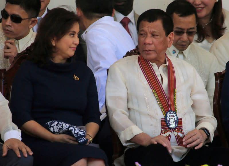 FILE PHOTO - President Rodrigo Duterte talks to Vice-President Leni Robredo during the Philippine National Police Academy graduation ceremony in Camp Castaneda