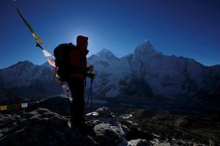 FILE PHOTO: A trekker stands in front of Mount Everest at Kala Patthar in Solukhumbu District