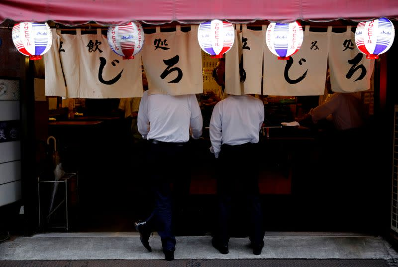 Men drink at a traditional bar after work in Tokyo