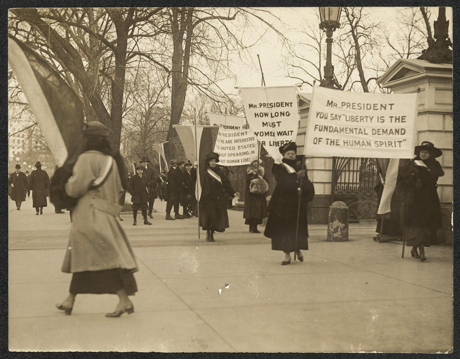"""<p>Suffragists picket with banners in front of the White House gates, Jan. 26, 1917. Banners read: """"Mr. President You Say Liberty Is The Fundamental Demand of the Human Spirit,"""" """"Mr. President How Long Must Women Wait for Liberty?"""" (Records of the National Woman's Party/Library of Congress) </p>"""
