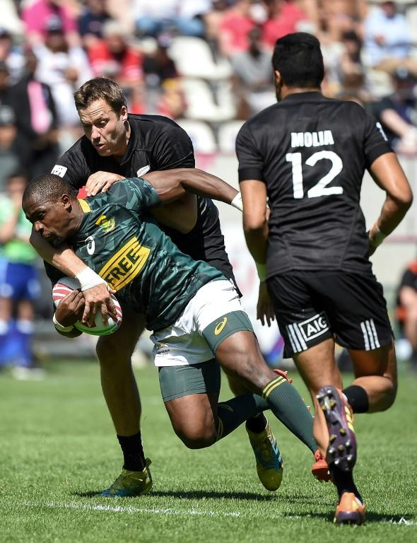 Both South Africa's Siviwe Soyizwapi (L bottom) and New Zealand's Tim Mikkelson (the tackler) will be in action for their countries at this weekend's Oktoberfest 7s in Munich. (AFP Photo/Lucas BARIOULET)